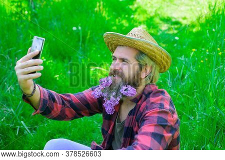 Handsome Man With Beard Of Flowers Making Selfie On Smartphone. Hipster Man With Flowers In His Bear