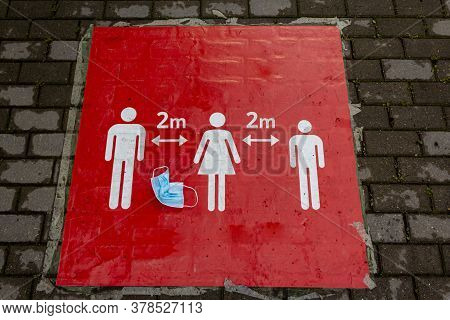 A Crumpled Protective Mask Lies On A Red Sign That Informs People To Keep A Social Distance. Sign In