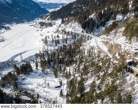 Aerial Image Of A Mountain Valley In Alps In Snowy Winter Season With Railway Viaduct At The Backgro