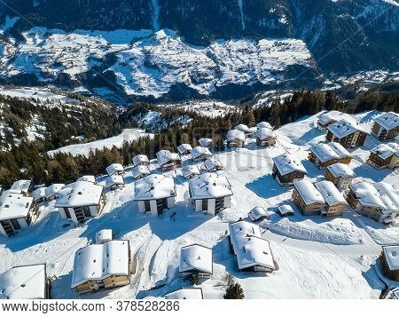 Aerial View Of Snow Covered Roofs Over The Traditional Chalets With Skiing Lift Station In The Villa