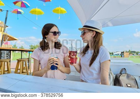 Girlfriends Teenagers Having Fun Drinking Soft Drinks While Sitting In An Outdoor Cafe On Sunny Summ