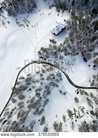 A Curvy Road Through The Mountain And Forest And Snow Field With Cross-country Ski Run In Winter