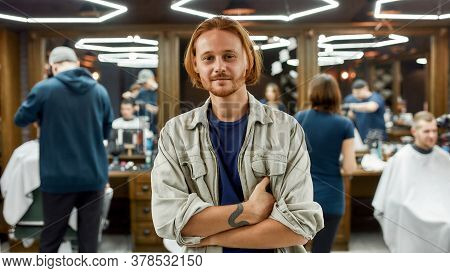 Visiting Barbershop. Portrait Of A Handsome Redhead Man Looking At Camera While Visiting Modern Barb