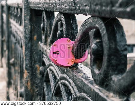Pink Heart-shaped Padlock Fastened To The Railing Of The Bridge. Wedding Tradition, Symbol Of Eterna