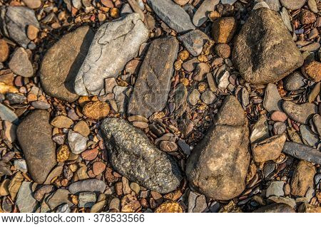 Looking Down On A Dry Part Of The Riverbed That Has Several Kinds Of Colorful Rocks And Stones With