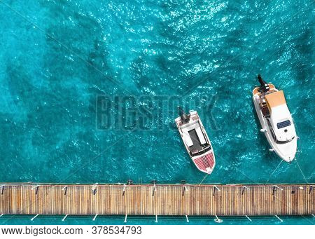 Tourist Pleasure Yacht And Motor Boat On The Sea Near The Pier. Top View