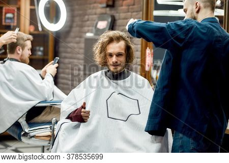 Happy Client. Portrait Of A Smiling Young Man Getting A Haircut In A Barbershop, Looking At Camera A