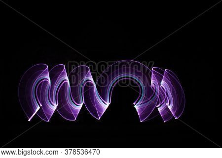 Curved Abstract Shape Made With A Light Saber Violet. Lightpainting Session At Night. Leds Effect.