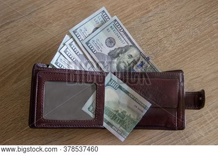 Dollars Fall From The Wallet That Lies On Table. Many Dollar Bills Lie In The Wallet. Men Wallet Wit