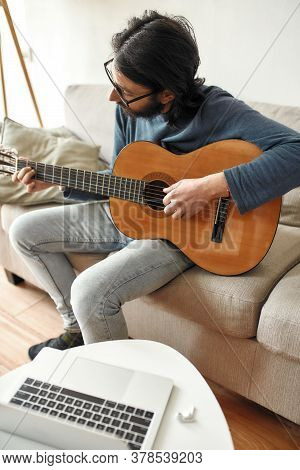 New Skill. Young Focused Man Sitting On Sofa At Home And Playing Acoustic Guitar, Watching Online Mu