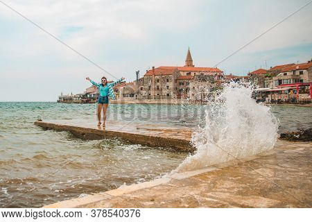 Woman Walking By Umag City Quay At Stormy Weather. Copy Space