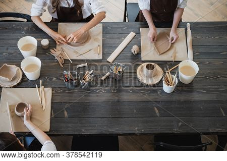 Top View Of Female Hands Sculpting Different Clay Products. Big Wooden Table With Pottery Tools On A