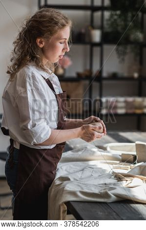 Female Master Kneads Clay Near Wooden Table On A Pottery Workshop