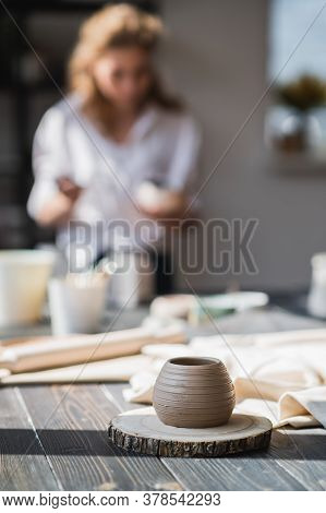 Newly Made On A Pottery Wheel Clay Pot On A Wooden Table. Woman Paint The Ceramic On A Background In