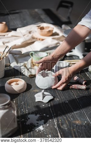 Female Hands Gently Putting The Finished Glazed Bowl On A Wooden Table With Different Pottery Tools.