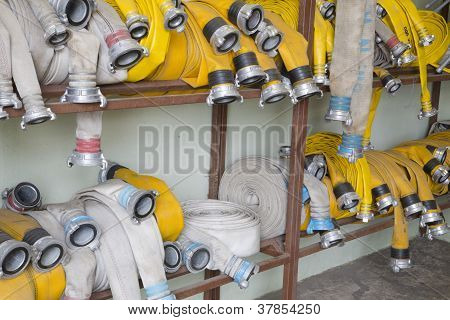 Yellow Firehose Are Hanging On Warehouse Shelfs