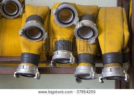 Zoomed Yellow Firehose Are Hanging In Warehouse
