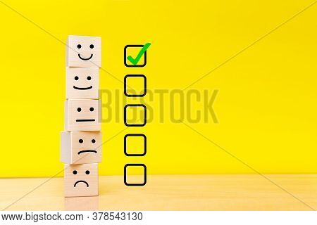 Customer Service Evaluation And Satisfaction Survey Concepts. Images Of Emoticons On Wooden Cubes. Y