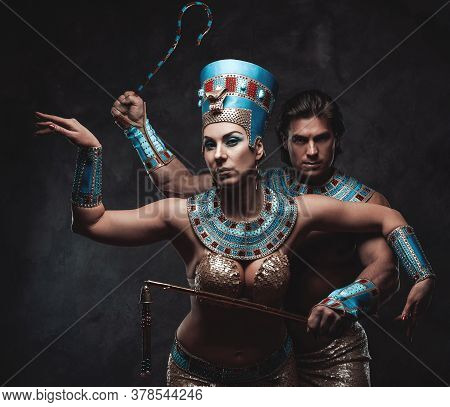 Couple In Traditional Blue And Gold Egyptian Costumes Posing In The Studio With Dark Walls