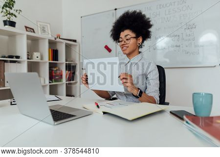 Smiling Afro American Female Teacher Showing A Blank Sheet Of Paper At Web Camera Of Her Laptop Whil