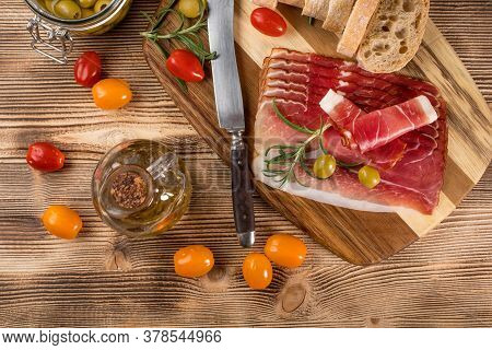 Thinly Sliced German Black Forest Ham With Sliced Ciabatta Bread, Tomato And Olives. Top View.