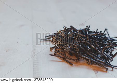 A Bunch Of Metal Nails On A Light Wooden Background, Space For Text