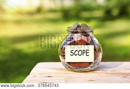 Scope. Glass Jar With Coins, On A Wooden Table, On A Natural Background.investment And Finance Conce