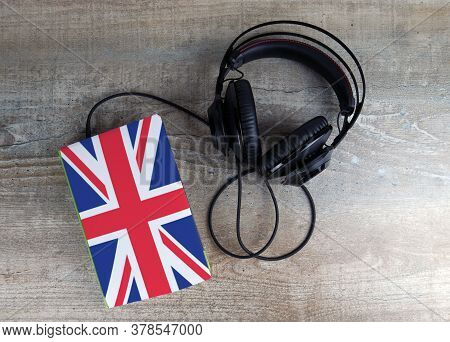 Headphones And Book. The Book Has A Cover In The Form Of Great Britain Flag. Concept Audiobooks. Lea