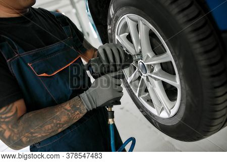 Cropped Shot Of Male Mechanic Screwing Or Unscrewing Car Wheel Of Lifted Automobile By Pneumatic Wre