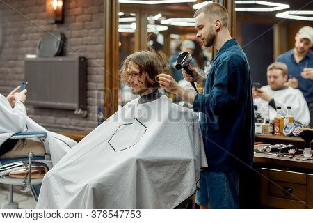 Barbershop Services. Professional Barber Drying Long Hair Of Young Hipster Guy Sitting In Armchair I
