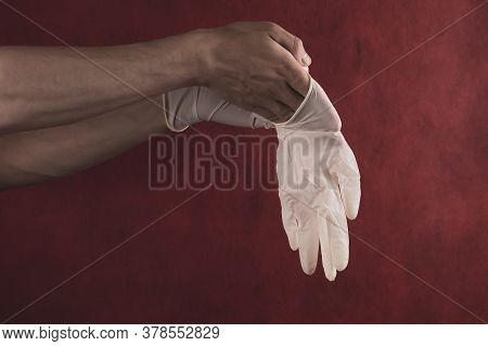 Hands In Medical Gloves On A Red Background. A Person Puts On Surgical Gloves