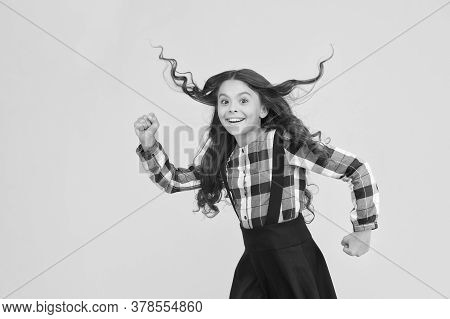 Make Haste Slowly. Energetic Girl Hurry To School. Small Child Wear Long Hairstyle Yellow Background