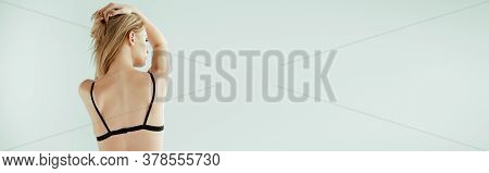Panoramic Orientation Of Woman In Black Bra Touching Hair Isolated On Grey