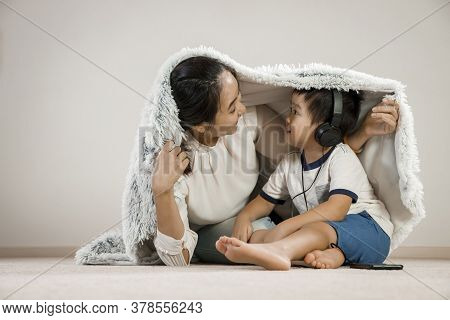 Asian Mother Hiding Under Blanket With Infant Child Wearing Headphones. Vietnamese Mom Smiling While