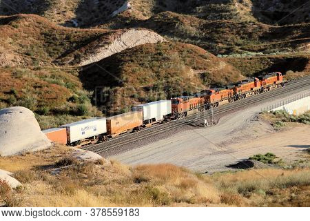 July 27, 2020 In Cajon Pass, Ca:  Freight Train With Four Locomotives Hauling Rail Cars Uphill Taken