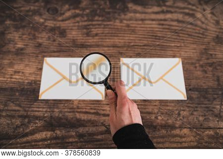 Inbox Organisation Conceptual Image, Email Icons Side By Side And Hand Holding Magnifying Glass To A