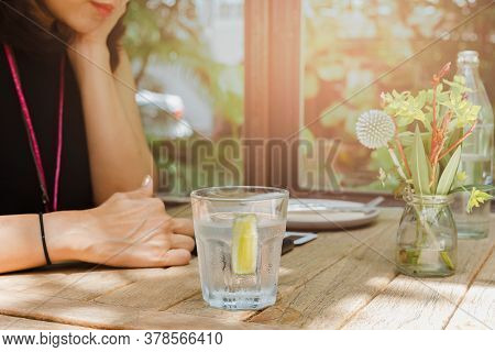 Healthy Nutrition Of Woman Drinking Water With Lemon In Restaurant.