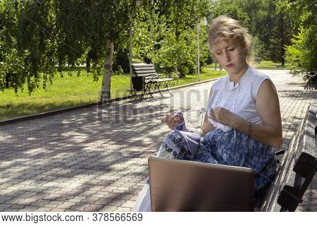 Woman In A Park Sits On A Bench Knitting Wool Clothes On Knitting Needles And Watching Lessons Or Te