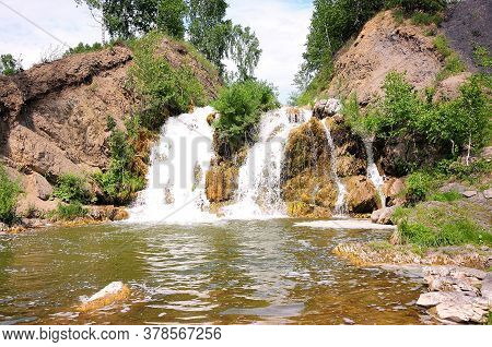 A Small Picturesque Waterfall Flowing Down Between The Mountains, Forming A Reservoir Surrounded By