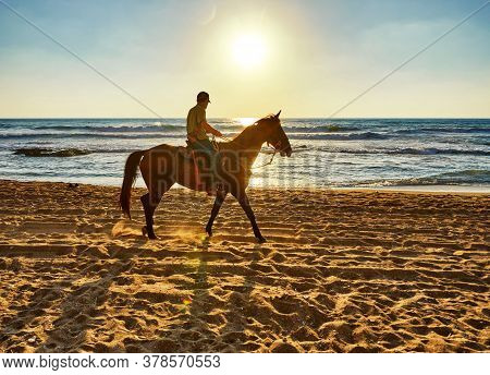 Arsuf, Israel - July 22, 2020: Horseback Riding Along The Mediterranean Sea Coast At Sunset.