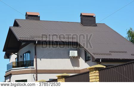 A House With A Saltbox, Catslide Brown Metal Roof With Snow Stoppers, Chimneys And Rain Gutter With