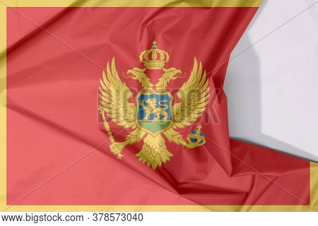 Montenegro Fabric Flag Crepe And Crease With White Space. A Red Field Surrounded By A Golden Border;