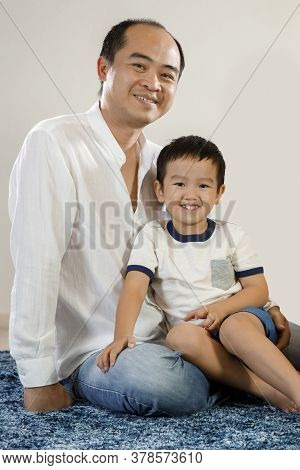 Happy, Smiling Asian Father And Son Portrait, Vietnamese Man Sitting On Floor With His Son In Arms,