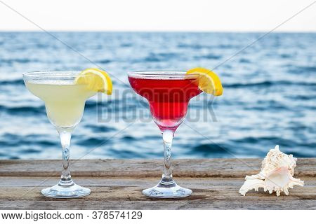 Two Summer Sweet Cocktails By The Sea. Cosmopolitan And Margarita In A Glass On The Pier. Mixed Alco