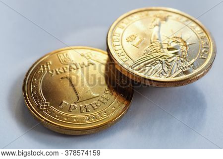 Ukrainian Coin In 1 Hryvnia And Us American One Dollar. Close-up. Hang Over A White Or Gray Paper Su