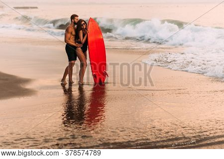 A Couple In Love On The Beach With A Surfboard. Beautiful Couple On The Island Of Bali. Happy Sporty