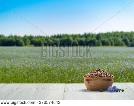 Flax Seeds On White Wooden Tabletop Over Blurred Flowering Field With Flax. Flaxseeds Oil Mock Up Wi