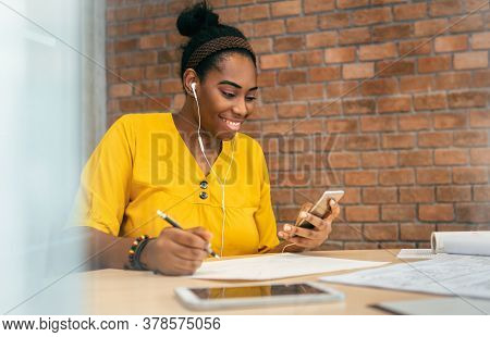 African Woman Designer Using Smartphone And Earphones For Listening To Music While Working At Workpl
