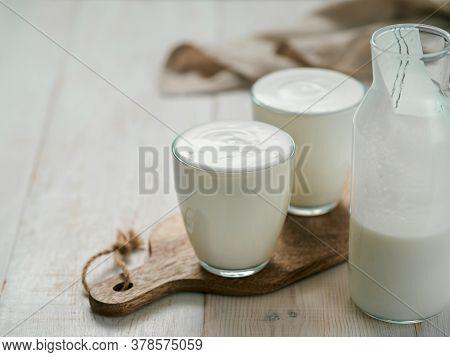 Kefir, Buttermilk Or Yogurt With Probiotics. Yogurt In Glass On White Wooden Background. Probiotic C