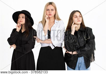 Three Young Beautiful Girls Are Thinking About Solving The Problem. Photo On A White Background